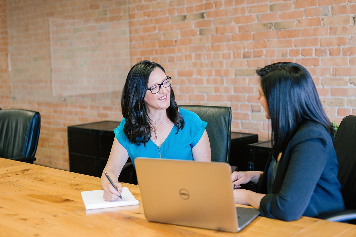 two professional women sit down at wooden desk for friendly meeting